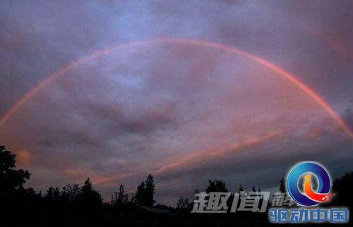 在美国俄勒冈州提嘉德市,清晨即将升起的太阳为天空中的一弧彩虹增添