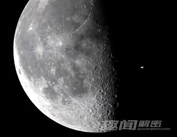 """4.空间站与月球合影 照片于2010年4月5日在位于美国佛罗里达州的肯尼迪航天中心拍摄。照片中的国际空间站成为一个亮点,与月球面面相对。给人的感觉是,拍摄时似乎有一只苍蝇趴在照相机镜头上。这幅照片是在""""发现""""号航天飞机发射升空前拍摄的。""""发现""""号携带一个满载补给的新货舱进入空间站,执行为期13天的太空任务。"""